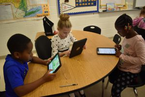 three kids using ipads in the classroom
