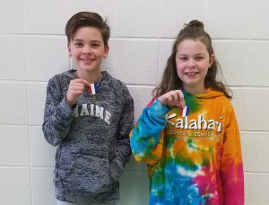 """Two students holding their NYSSMA """"perfect-score"""" medals."""