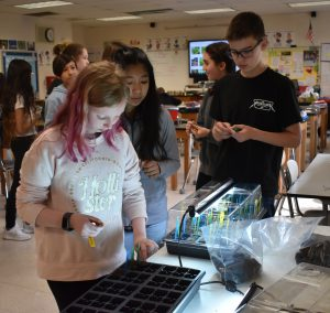students in science class planting seeds