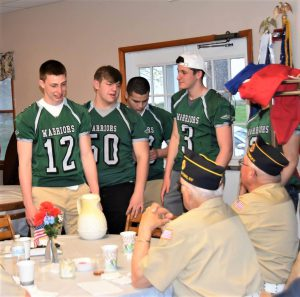 Four football players talk with veterans over dinner