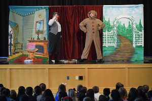 Two actors on stage act out a scene of the Velveteen rabbit. Students sit on the floor watching.
