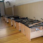 Row of new sinks in gym. They are to be installed in classrooms
