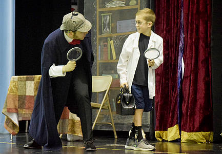 Actor dressed as Sherlock Holmes and student volunteer dressed as Watson look for clues with large magnifying glasses on stage