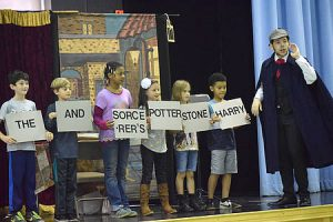 Students on stage hold signs with scrambled words that are to form a phrase (Harry Potter and the Sorcerer's Stone. Actor dressed as Sherlock Holmes calls on the audience to guess at the porper order of the words.