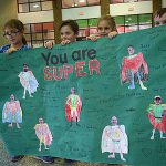 "Four students standing in the cafeteria present a large poster titled, ""you are super"" to the custodial staff. It depicts their faces pasted onto the bodies of superheros"