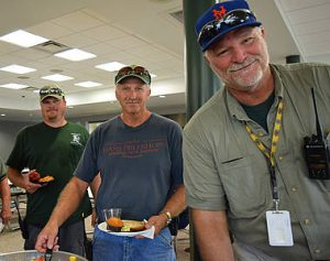 Custodial staff sampling breakfast buffet and posing for camera in cafeteria