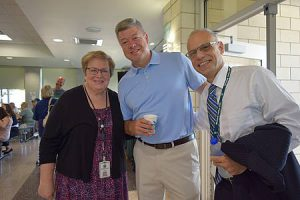 Teacher and administrators pose for camera in cafeteria