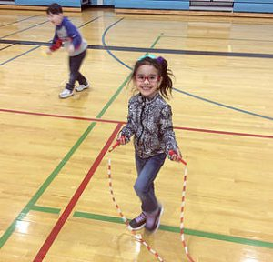 Student smiles at camera while jumping rope in the gym
