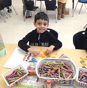 student at this desk playing with multi-color fish-shaped snacks; three baskets of crayons are in the foreground.