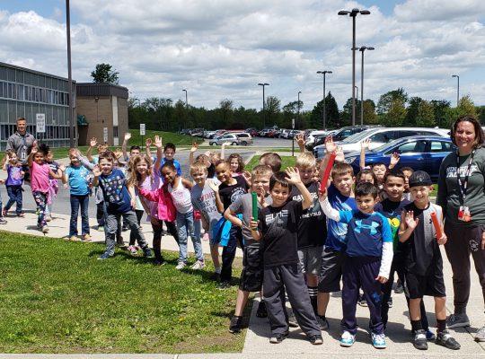 1st grade students waving to camera