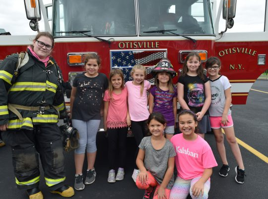 Students posing in front of fire truck