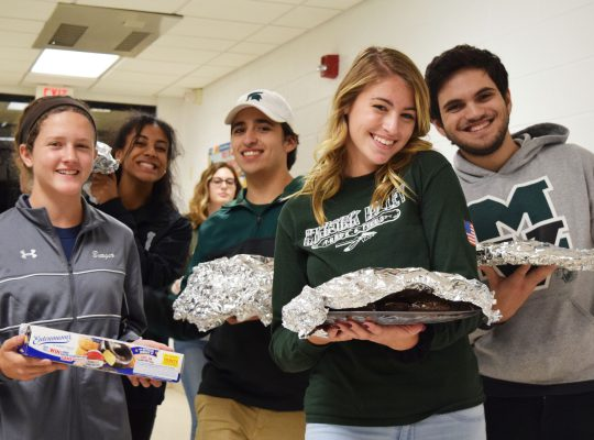 Students holding baked goods