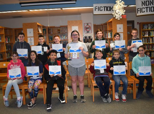 Middle School students displaying achievement awards