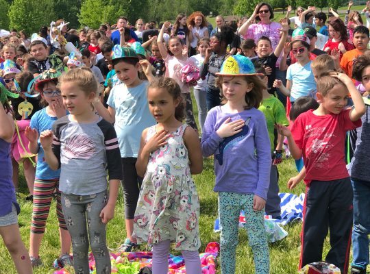 Students saying pledge of allegiance outside