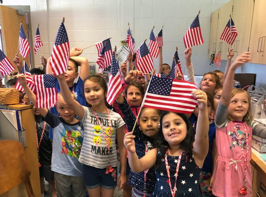 Students holding up flags at Flag Day