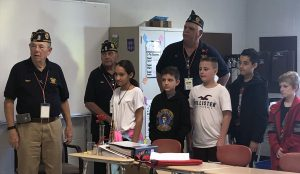 veterans and students standing by a table