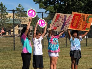 students holding signs at outdoor assembly