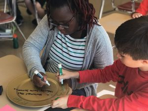 students writing words on a plate