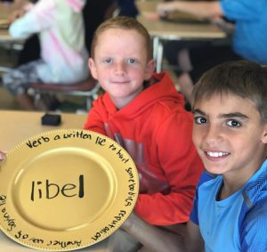 students holding a plate with words
