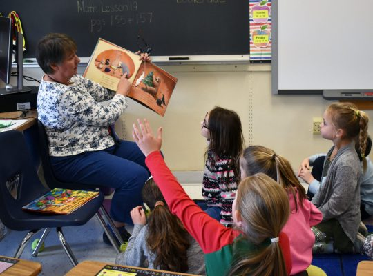 teacher reading to little students