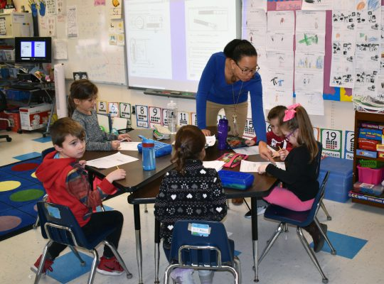 kindergarten teacher working with students
