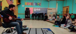 musician plays guitars for students