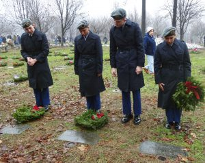 four cadets laying wreaths a gravesite