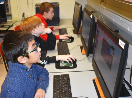 three students at computers