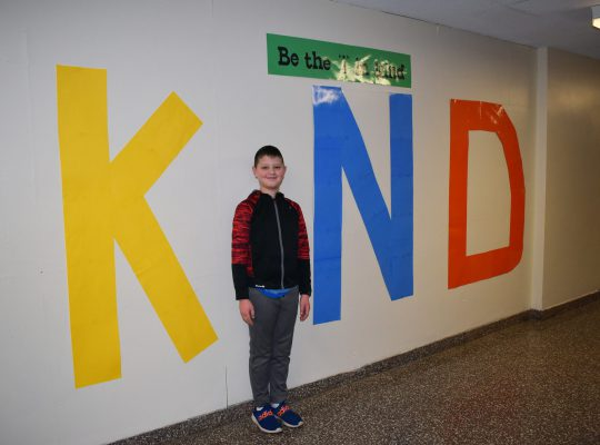 Boy standing in front of a kind sign