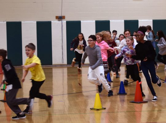 kids running an obstacle course in gym
