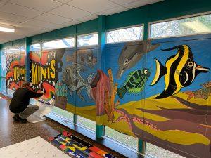 artist installing the vinyl mural