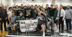 Students and wrestling coach with sign