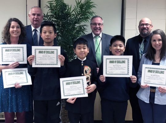 students and teachers holding certificates with members of the Board of Education and administration