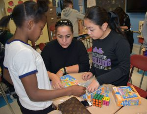 students and visitors making a puzzle