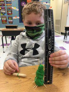 student makin playdoh toothpick trees