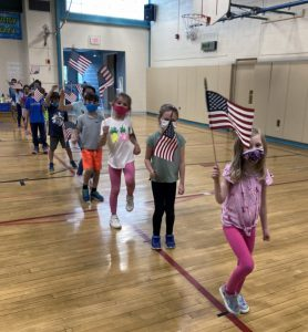 kids marching with flags in gym class
