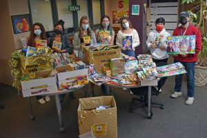 students with boxes of donated crayons and coloring books