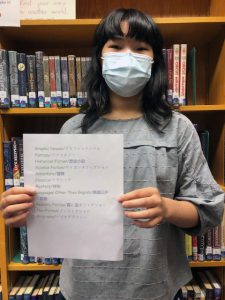 Student holding Japanese character translation signs